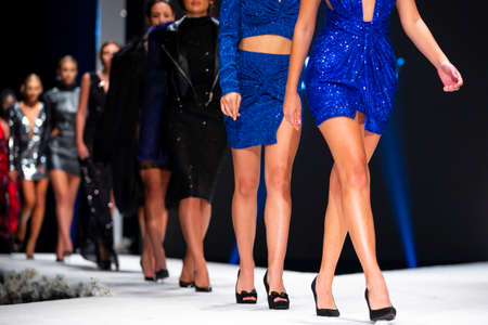 Female models walk the runway in beautiful blue designer dresses during a Fashion Show. Fashion catwalk event showing new collection of clothes. Unrecognizable people. High heels shoes. Legs only. 免版税图像