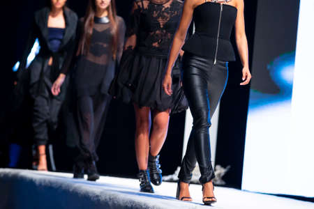 Female models walk the runway in beautiful designer dresses during a Fashion Show. Fashion catwalk event showing new collection of clothes. High heels shoes. Legs only. Black Leather Leggings Bottoms. 免版税图像