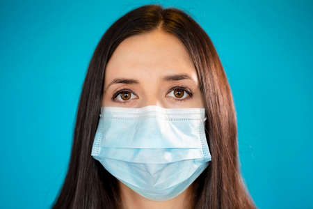Young woman wearing a protective surgical face mask during the Coronavirus disease COVID-19 outbreak epidemic. Close up portrait with a single use blue protection mask on the face shot in a studio. 免版税图像 - 144567719