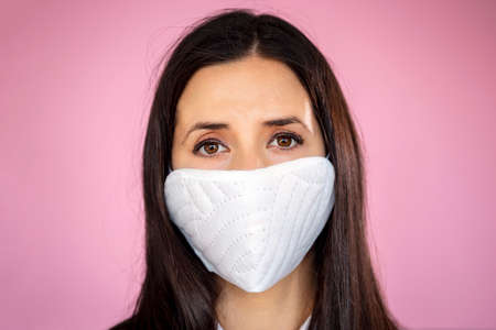 Young woman wearing a protective face mask during the Coronavirus disease COVID-19 outbreak epidemic. Close up portrait with a multiple use white protection mask on the face shot in a studio. 免版税图像