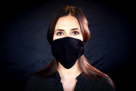 Young woman wearing a protective black leather face mask during the Coronavirus disease COVID-19 outbreak epidemic. Close up studio portrait on a black background with a multiple use protection mask on the face.
