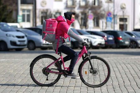 Sofia, Bulgaria - 30 March, 2020: A worker at Foodpanda online food delivery company rides a bicycle with food to an address. Wearing a protective face mask during the Coronavirus disease COVID-19 outbreak epidemic.
