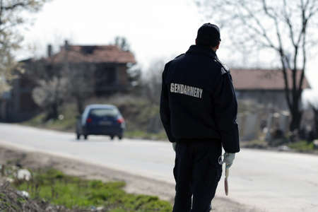 A police officer in a gendarmery uniform stands on his post near a checkpoint. Imagens
