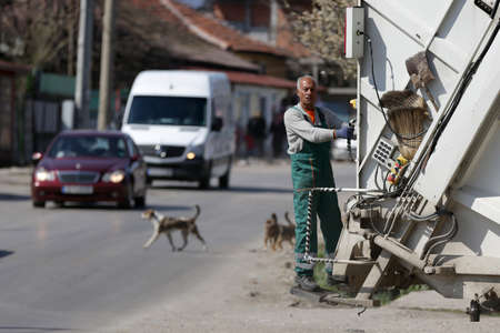 Sofia, Bulgaria - 11 April, 2020: Garbage truck worker travels on the vehicle during his work shift, 免版税图像 - 144640876