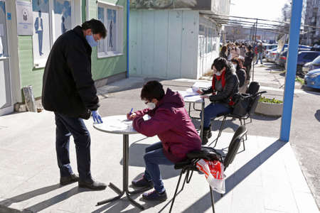 Sofia, Bulgaria - April 8, 2020: People wearing face masks in an attempt to prevent the spread of coronavirus disease COVID-19 wait in line in front of an office of the labor bureau. 免版税图像 - 144640878