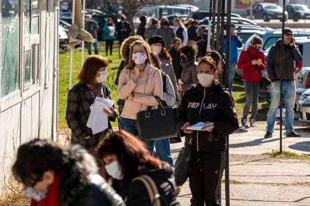 Sofia, Bulgaria - April 8, 2020: People wearing face masks in an attempt to prevent the spread of coronavirus disease COVID-19 wait in line in front of an office of the labor bureau. 免版税图像 - 144640879