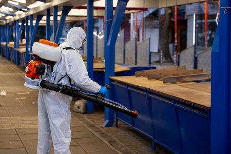 Worker sprays disinfectant outside of ? food market against the spread of coronavirus disease COVID-19. 免版税图像 - 145540825