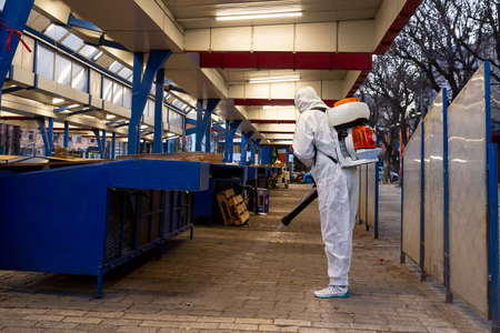 Worker sprays disinfectant outside of ? food market against the spread of coronavirus disease COVID-19. 新闻类图片