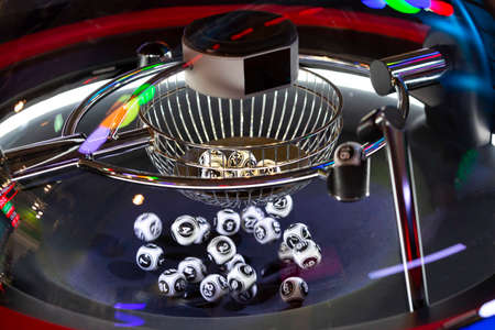 Black and white lottery balls in a rotating bingo machine. Lottery balls in a sphere in motion. Gambling machine and euqipment. Blurred lottery balls in a lotto machine. Number 16. 免版税图像 - 147526603