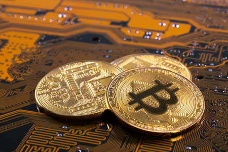 Virtual cryptocurrency money Bitcoin golden coins on a computer printed circuit board PCB. The future of money. Computational equipment. Yellow and green mother board.