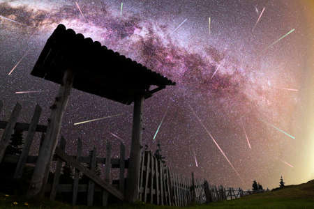 A view of a Meteor Shower and the purple Milky Way with wooden entrance door with a roof and fence silhouette in the foreground. Night sky nature summer landscape. Perseid Meteor Shower observation. Colorful shooting stars. 免版税图像