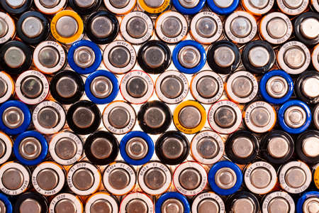 Multiple used AA alkaline batteries are seen arranged in a pile. Closeup front view from the minus side of the battery. 免版税图像 - 147526616