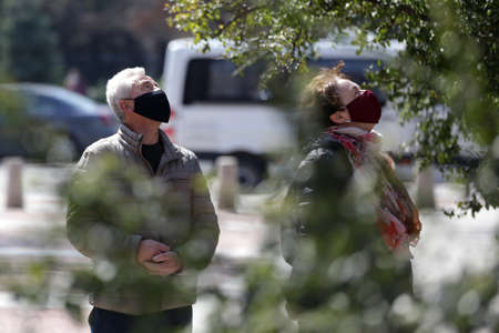 Sofia, Bulgaria - 30 March, 2020: A woman and a man wearing multiple use protective face masks during the Coronavirus disease COVID-19 outbreak epidemic walk in a park in Sofia. 免版税图像 - 146337554