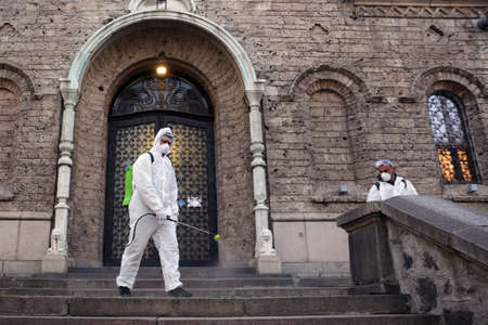 Sofia, Bulgaria - 11 April, 2020: Worker sprays disinfectant outside of Sveta Nedelya Church against the spread of coronavirus disease COVID-19.