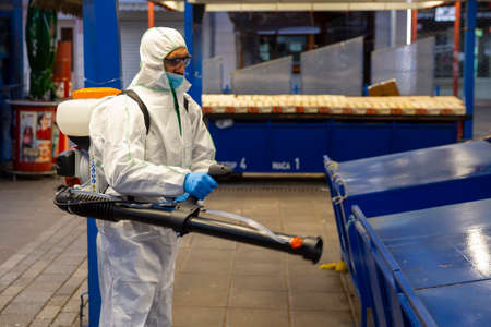 Sofia, Bulgaria - 7 April, 2020: Worker sprays disinfectant outside of ? food market against the spread of coronavirus disease COVID-19. 免版税图像 - 146337557