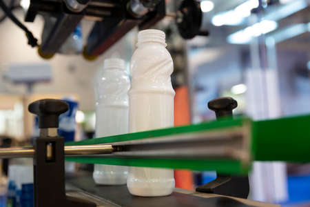 White milk bottles on a production line in a dairy farm. 免版税图像 - 148774016