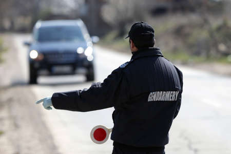 A police officer in a gendarmery uniform stops a car for a road check.
