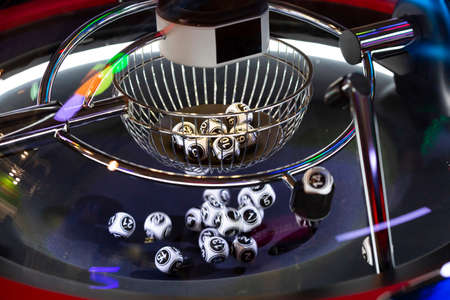 Black and white lottery balls in a rotating bingo machine. Lottery balls in a sphere in motion. Gambling machine and euqipment. Blurred lottery balls in a lotto machine. Number 14.
