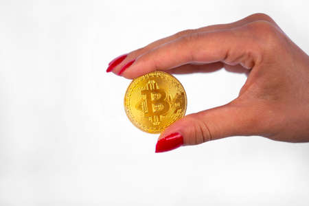 Virtual cryptocurrency money Bitcoin golden coin in the right hand of a woman with red nail polish. The future of money. Isolated on a white background. 免版税图像