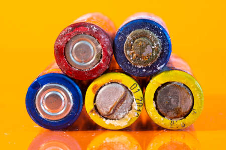 Multiple used bad AA alkaline batteries are seen arranged in a pile on a reflective orange surface. Closeup front view from the minus side of the battery. 免版税图像 - 150020662