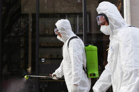 Sofia, Bulgaria - 11 April, 2020: Workers spray disinfectant outside on a street against the spread of coronavirus disease COVID-19. 免版税图像 - 148825672