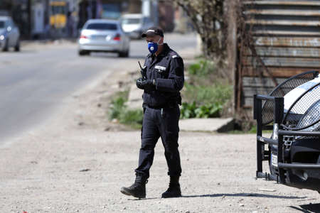 Sofia, Bulgaria - 11 April, 2020: A police officer in a gendarmery uniform with protective face mask against the spread of coronavirus disease COVID-19 stands on his post near a checkpoint.