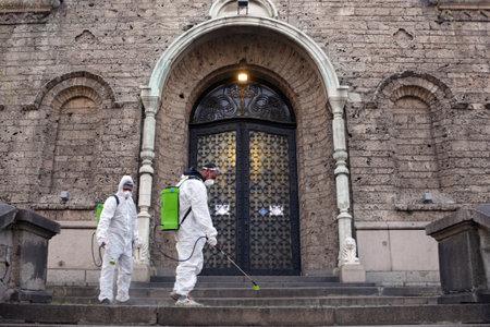 Sofia, Bulgaria - 11 April, 2020: Workers spray disinfectant outside of Sveta Nedelya Church against the spread of coronavirus disease COVID-19.