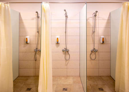 Three new showers with curtains and soap dispensers. 免版税图像 - 150796103