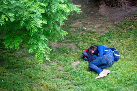 Homelsess person sleeps in a park under a tree with a face mask on. 免版税图像 - 150832631