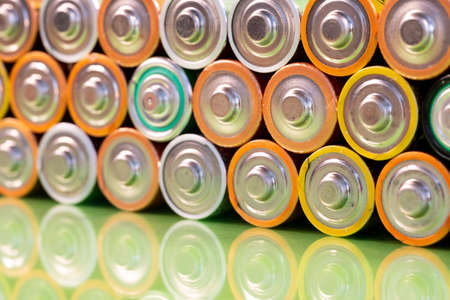 Multiple used AA alkaline batteries are seen arranged in a pile on a reflective green surface. Closeup front view from the plus side of the battery. 免版税图像 - 150832633