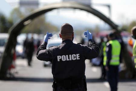Policeman navigates cars through a police checkpoint.