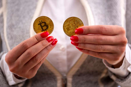 Virtual cryptocurrency money Bitcoin golden coins in the hands of a woman with red nail polish. The future of money.
