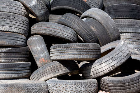 Old and used car tyres on a pile. 免版税图像
