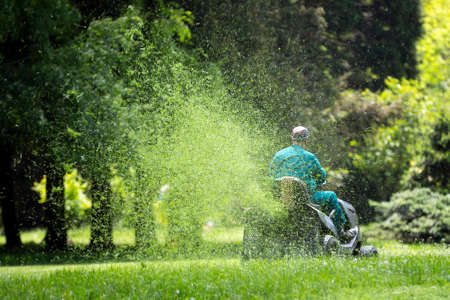 Worker with a gasoline tractor lawn mower mows the fresh green lawn. 免版税图像