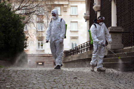 Sofia, Bulgaria - 11 April, 2020: Workers spray disinfectant outside of Sveta Nedelya Church against the spread of coronavirus disease COVID-19. 免版税图像 - 150896815