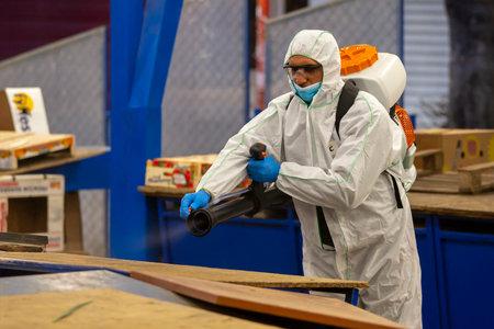 Sofia, Bulgaria - 7 April, 2020: Worker sprays disinfectant outside of ? food market against the spread of coronavirus disease COVID-19.
