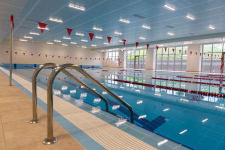 Indoor swimming pool full of water with ladder on the side. 免版税图像 - 150806847