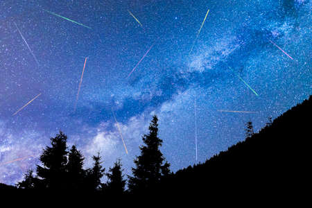 A view of the stars of the blue Milky Way with pine trees forest silhouette in the foreground. Night sky nature summer landscape. Perseid Meteor Shower observation. Colorful shooting stars. 免版税图像
