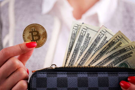 Virtual cryptocurrency money Bitcoin golden coins in the left hand of a woman with red nail polish and a purse. The future of money. US dollars.