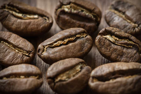 Few roasted cofee bean on wooden background