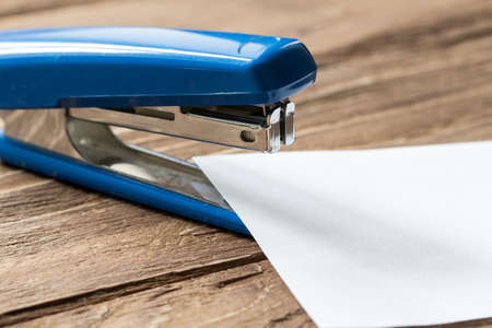 engrapadora: stepler azul y hoja de papel sobre fondo de madera Foto de archivo