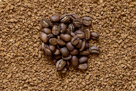 Pile of cofee seeds on instant granulated cofe background