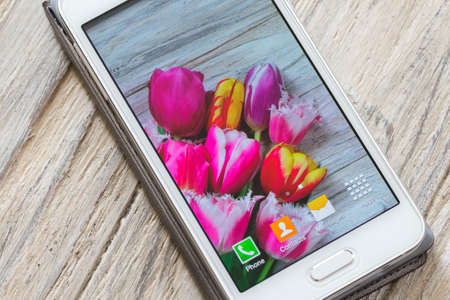 White smartphone with flowers on screen isolated on wooden background