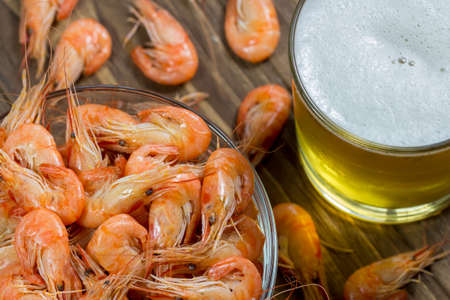 top veiw: Boiled shrimps in a glass bowl and beer in a glass top veiw, close-up