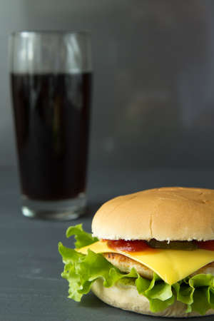 Cheeseburger and glass of cola on grey wooden surface, closeup