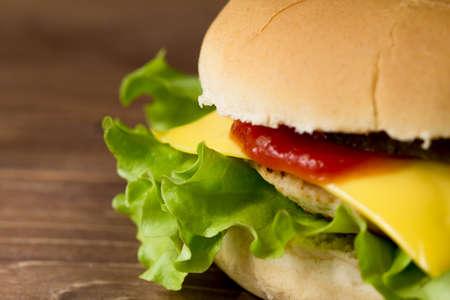 produits alimentaires: Tasty fresh cheeseburger on wooden surface closeup, macro