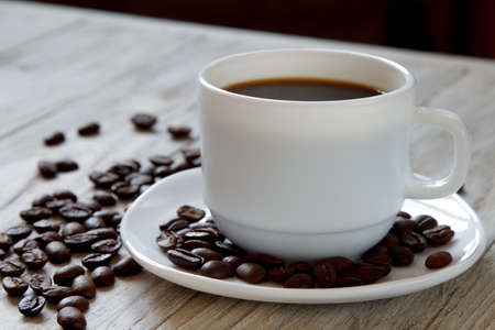 Black coffee in a mug and roasted beans on wooden suface, close-up
