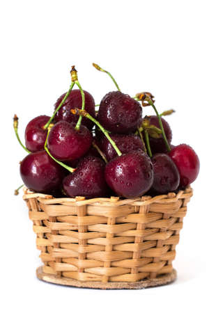 Full basket of red cherries with water drops on a stem close up, white background