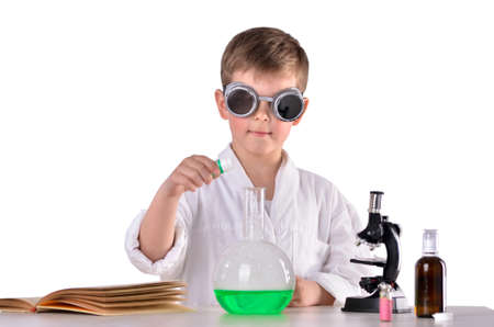 Scientist boy in black protective glasses put chemistry reagents in a flask Stock Photo