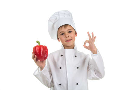 Boy in chef uniform making ok gesture and holding red pepper